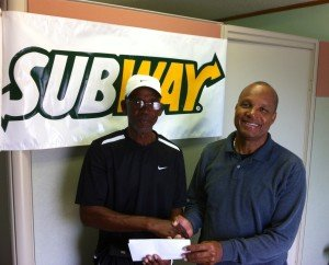 SUBWAY owner,  Shuffel Hepburn presents tournament director and Grand Bahama Tennis  Association Treasurer,  Coach Gully Bowe, with a check for the sponsorship of the 8th annual SUBWAY Junior Tennis Tournament.